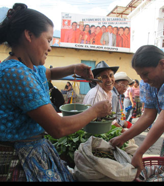 Photo of a woman weighing vegetables in Guatemala
